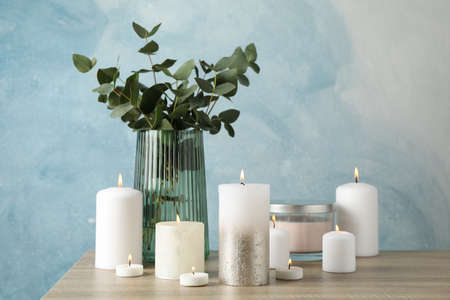 Burning candles and vase with eucalyptus on wood table against blue background, space for text