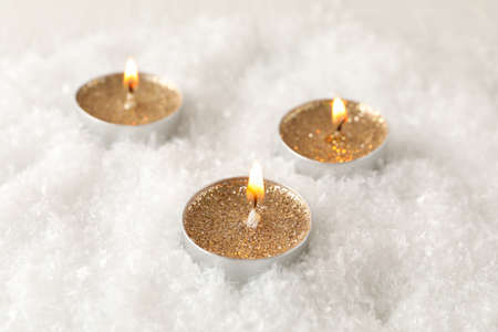 Candles with glitter on snow background, close up