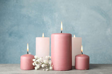 Group of burning candles and flower against blue background, close up