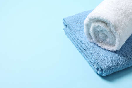 Folded towels on blue background, close up and space for text
