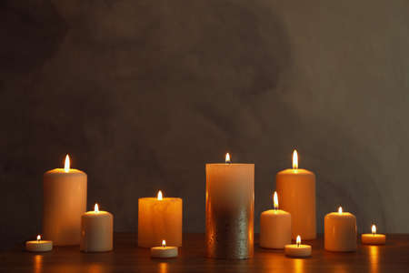 Group of burning candles on black table, space for text