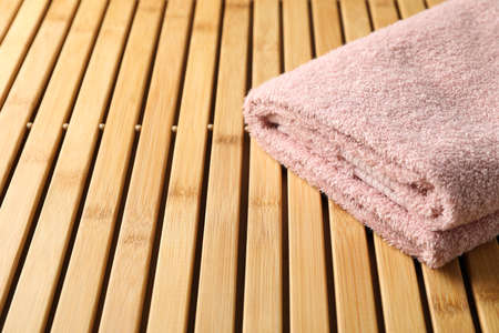 Folded pink towel on bamboo background, close up and space for text Фото со стока