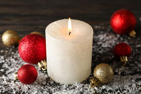 Burning candle and christmas balls on wooden background with snow, close up