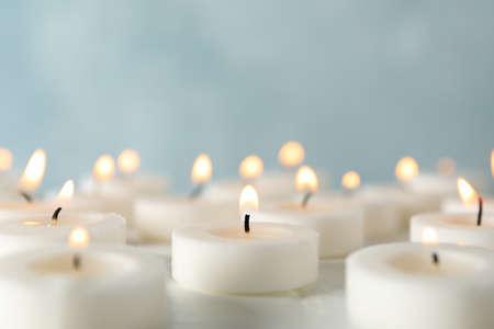 Groep brandende kaarsen tegen blauwe achtergrond, close-up Stockfoto