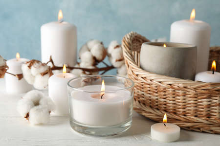 Burning candles, basket and cotton on white wooden background, close up Zdjęcie Seryjne