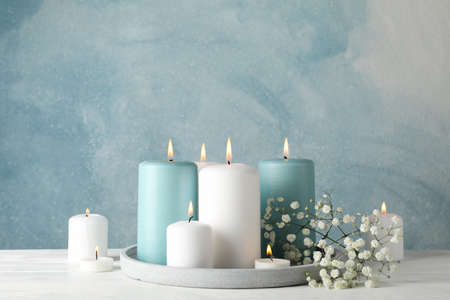 Burning candles, tray and flower against blue background, space for text Zdjęcie Seryjne