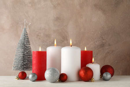 Burning candles, christmas tree and balls against brown background, space for text Zdjęcie Seryjne