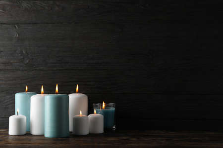 Different burning candles on wooden background, space for text Zdjęcie Seryjne
