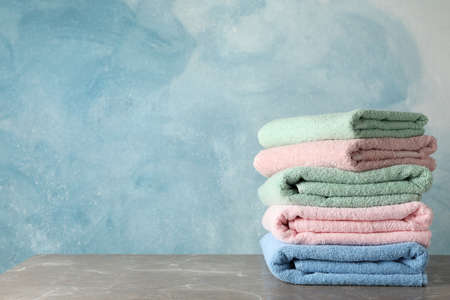 Stack of color towels on grey table against blue background, space for text