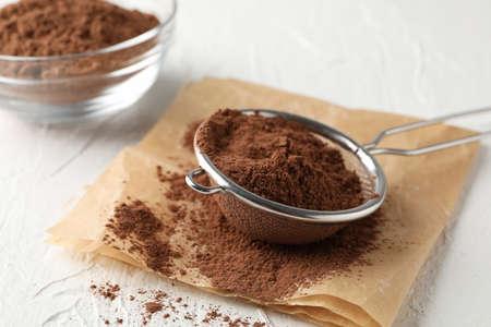 Recipiente de vidrio y colador con cacao en polvo, papel de hornear sobre fondo blanco, cerrar