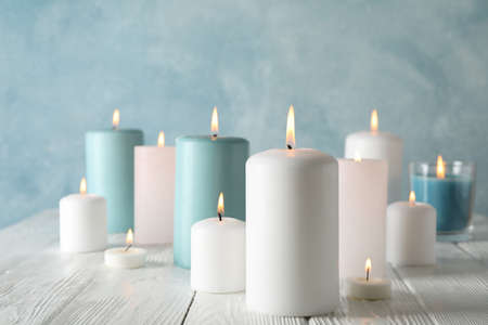 Different burning candles against blue background, space for text Zdjęcie Seryjne