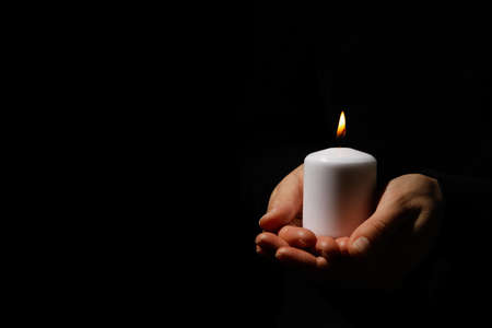 Woman holds candle on black background, space for text