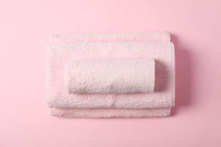 Composition with folded towels on pink background, top view