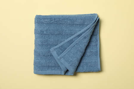 Blue towel on beige background, top view and close up