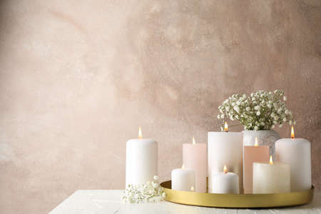 Burning candles, tray and flower on white table, space for text Zdjęcie Seryjne