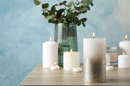 Burning candles and vase with eucalyptus on wood table against blue background, close up