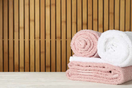 Folded towels on wooden table against bamboo background, space for text Фото со стока