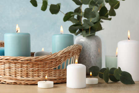 Burning candles, basket and vase with eucalyptus against blue background, close up Zdjęcie Seryjne