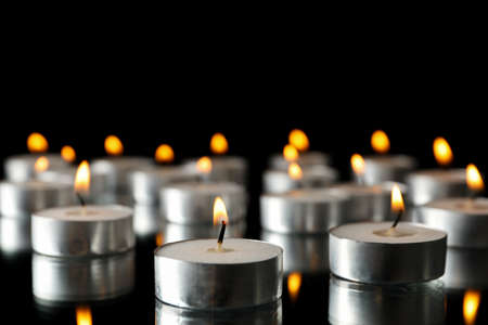 Group of burning candles on black background, space for text