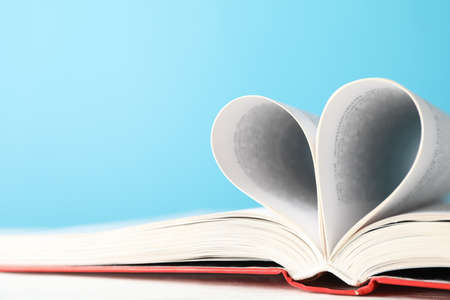 Heart made of pages. Book against blue background, space for text Stock fotó