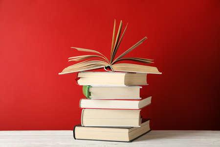 Stapel boeken tegen rode achtergrond, ruimte voor tekst