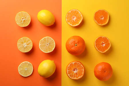 Juicy mandarins and lemons on two tone background, top view