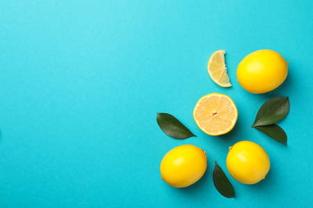 Delicious lemons on turquoise background, space for text
