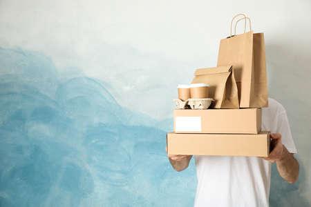 L'homme tient des boîtes, des tasses à café et des emballages en papier à l'intérieur, de l'espace pour le texte