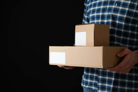 Man in shirt hold blank boxes against black background, space for text Archivio Fotografico