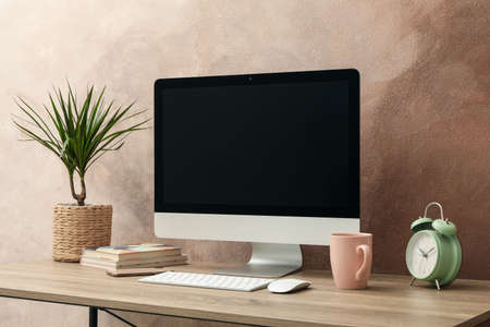 Workplace with computer and plant on wooden table. Light brown background