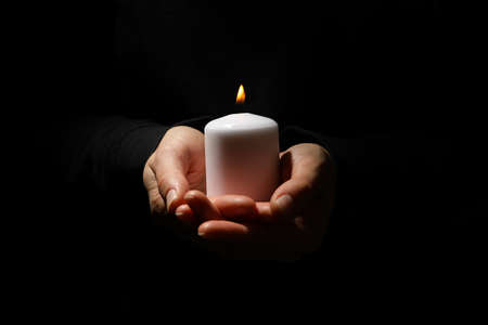 Woman holds candle on black background, front view
