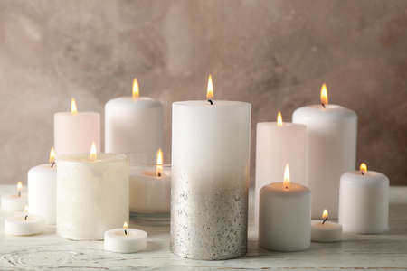 Different burning candles against brown background, close up