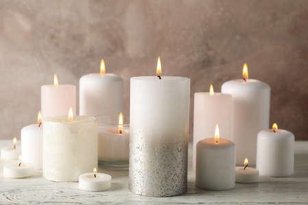 Verschiedene brennende Kerzen vor braunem Hintergrund, Nahaufnahme