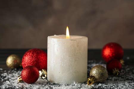 Velas encendidas y bolas de navidad sobre fondo de madera con nieve, cerrar