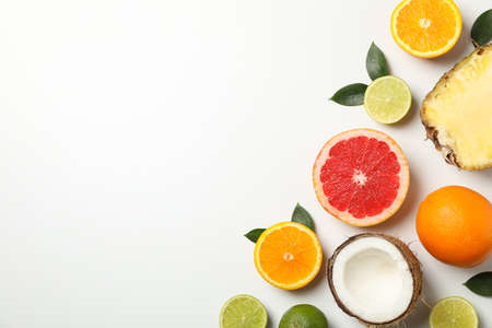 Flat lay with exotic fruits on white background, space for text