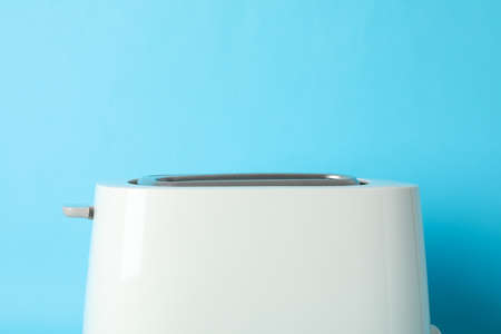 Toaster on blue background, close up and space for text