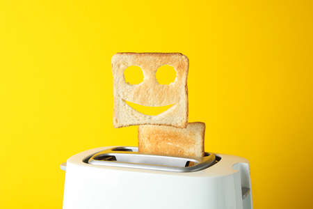 Toaster and toast with happy face on yellow background, space for text