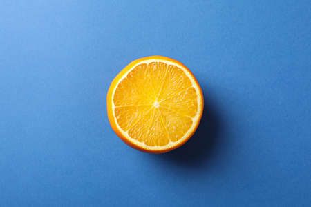 Half of juicy orange on blue background, space for text Stock Photo