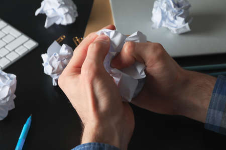 Man crumpling paper on black table with paper balls and stationery, close up Stok Fotoğraf