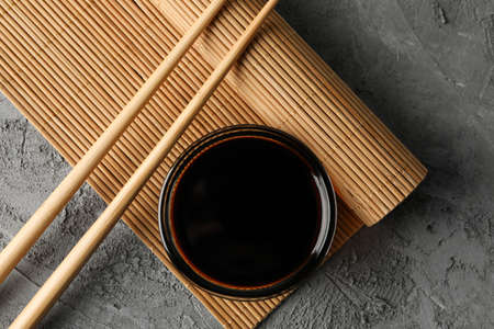 Bowl of soy sauce on gray background, space for text. Top view