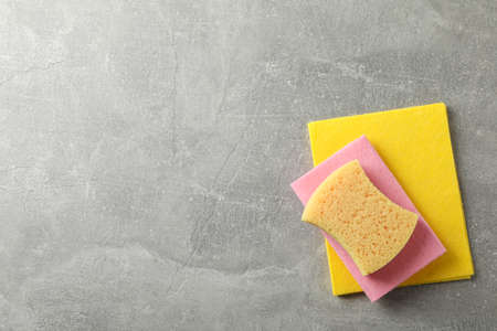 Sponges for washing dishes on grey background, top view