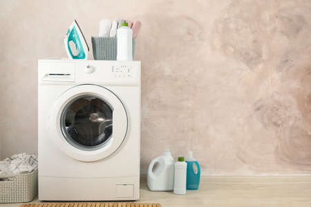 Laundry room with washing machine against light brown wall Reklamní fotografie