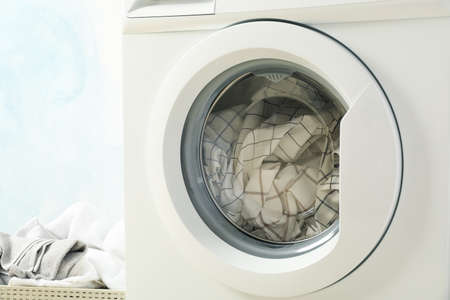 Laundry in a washing machine and in basket, close up