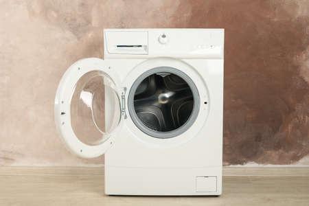 Modern washing machine against brown wall. Open machine