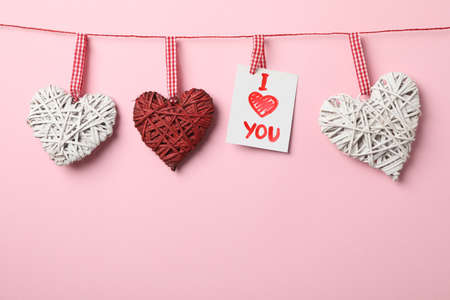 Hanging hearts and inscription I love you on pink background, space for text Banco de Imagens