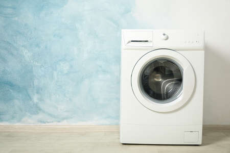 Modern washing machine against blue background, space for text