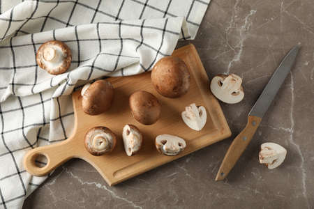 Champignons, knife, board and towel on grey background, top view
