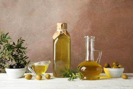 Bottle and jug with olive oil and olives against brown background, space for text