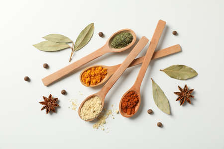 Spoons with different spices and ingredients on white background, top view Stock Photo