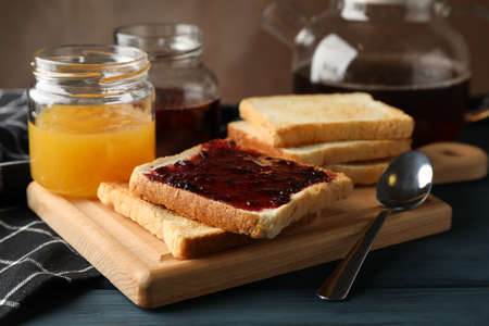 Toasts, jam and tea on wooden background, close up